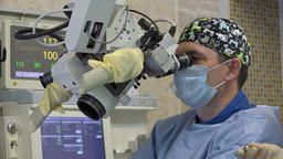 A male surgeon performs a microscopic operation on a patient's ENT organs using Footage