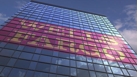 WELLS FARGO logo against modern building reflecting sky and clouds, editorial Live Action