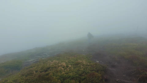 Wanderer man as stranger walking a hilly road as climbing a mountain in a cold windy day as the wind Footage