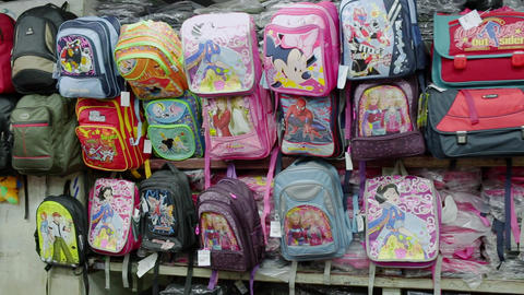 Back to school concept. Collection of multi-colored kids school bags on the store shelfs Footage