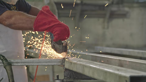 Slow motion of a worker using metal grinder with sparks flying at a metal shop Live Action
