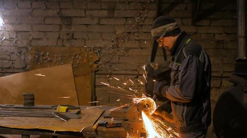 Blacksmith sawing metal with hand circular saw Live Action