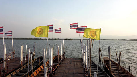 Phayao, Thailand - 2019-03-08 - Many Thailand and Buddhist Flags Flying on Pier Live Action