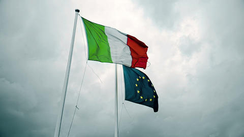 waving fabric texture of the flag of italy and union europe on sky with clouds Live Action