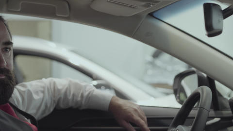 Portrait attractive successful bearded man sitting in the vehicle and inspects Footage