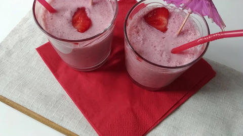 Two glasses fruit smoothies milkshake moving down Live Action