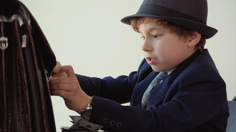 Young boy looks like a boss can't close his briefcase sitting at office Footage