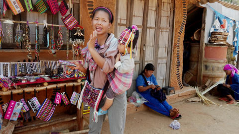 Mae Saiong. Thailand - 2019-03-11 - Woman With Baby On Back Tried To Sell Her Live Action