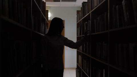 4K Silhouette Of A Girl Looking At The Books Before A Shelf In The Library Footage