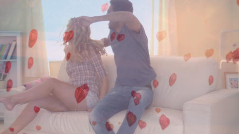 Happy couple jumping on the sofa with digital hearts on the foreground Animation
