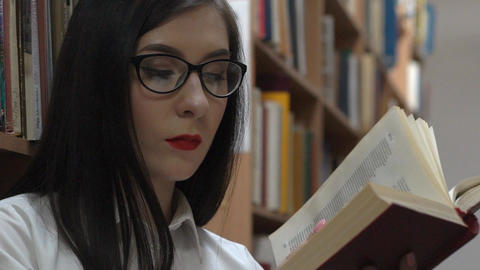 Beautiful Young Caucasian Woman Reading In Library Between The Stacks Footage