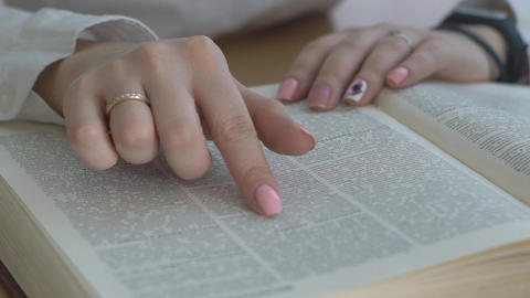 Close Up Shot Of Woman's Hand Reading A Book Indoors Live Action