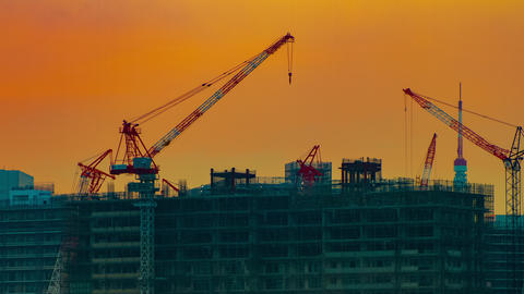 A time lapse of moving cranes at the under construction in Tokyo at dusk Footage
