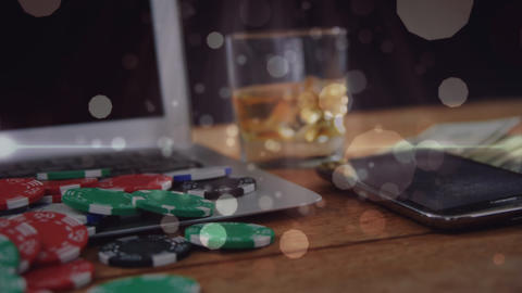 Wooden table with glass of whisky, banknotes, gambling chips, computer, mobile phone and animated bu Animation