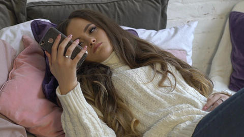 Young Girl Sitting On The Bed And Watching Content On Smart Phone Live Action