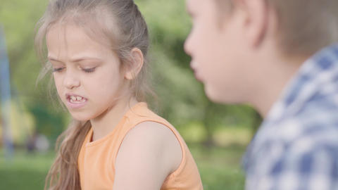 Portrait of adorable boy and girl sitting in the park, talking and having fun. A Footage