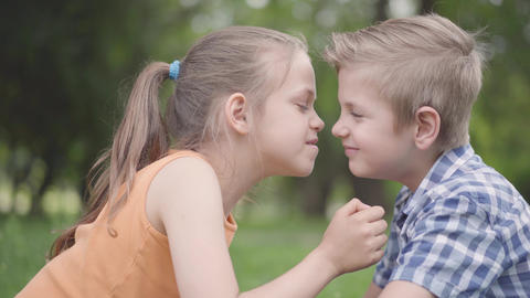 Side view of cute boy and girl sitting in the park, rubbing their noses and Live Action