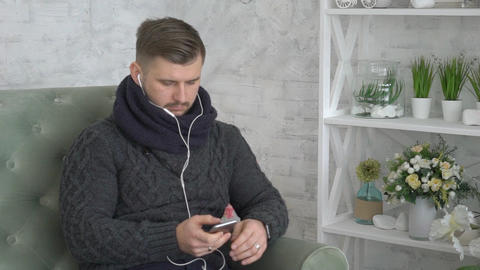 Young Man Sending Sms Message Texting On Mobile Phone Sit On Sofa In Living Room Live Action