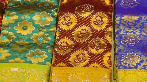 Shot of Indian Traditional Women's Sari clothing on Market. Various multi-colored women's clothing Footage