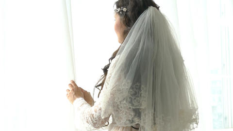 Beautiful Bride In A Dress Stands By The Window Dreaming, Smiling Charmingly Footage