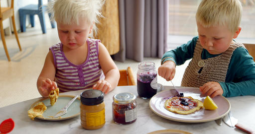 Siblings eating pancakes at dining table 4k Live Action