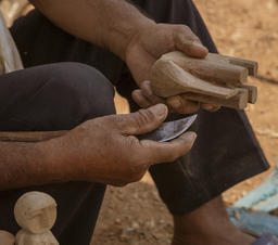 Man Carves Wooden Elephant Toy for Sale Photo