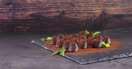 Sprinkling with cocoa chocolate truffles on slate Live Action