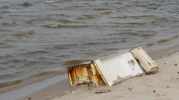 Old, rusty fridge on a beach. Human activity. Littering the natural environment Live Action