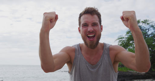 Strong fitness man on beach cheering celebrating flexing arms screaming excited Footage