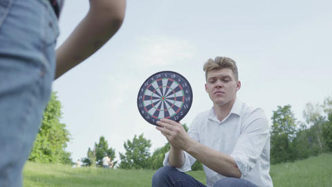Cheerful young father holding darts while his son throwing darts on a magnet in Footage
