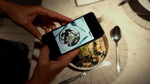 Person taking picture of food on phone at dinner Footage