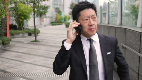 Japanese businessman talking on a cell phone ライブ動画