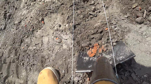 Worker digs a shovel trench at a construction site. Layout foundation with a Live Action