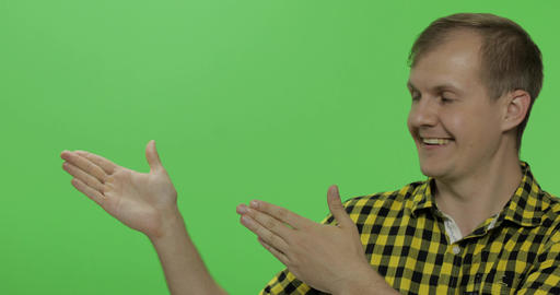 Caucasian man in yellow shirt showing something. Place for your logo or text Footage