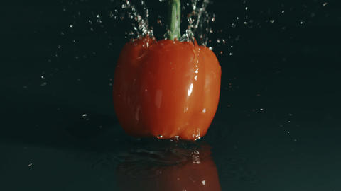 Single red bell pepper splashes in shallow water. Slow motion, shot on Red Footage