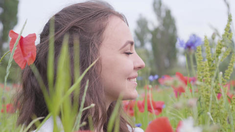 Close-up portrait cute girl sitting in poppy field. Cute happy smiling girl Live Action