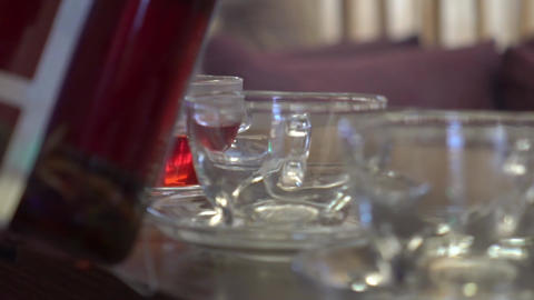 Slow Motion Pouring Red Herbal Tea From Glass Teapot In Cup Live Action