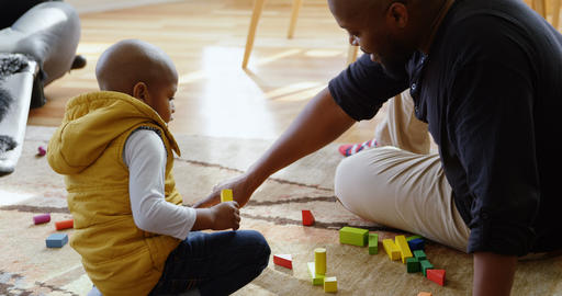 Father and son playing with building blocks in a comfortable home 4k Live Action