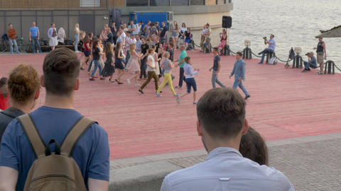 people dance at street party on city piers in early evening Footage