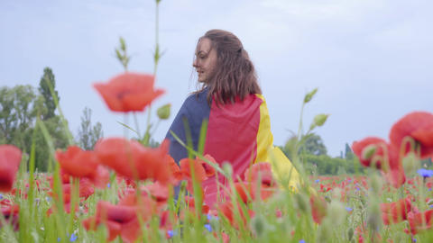 Cute adorable cute young woman standing in a poppy field holding flag of Germany Live Action