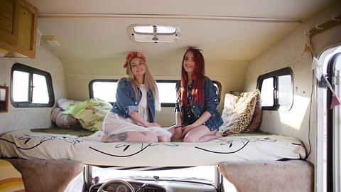 Couple of young women dressed in Indie and Boho styles sitting in auto trailer Footage
