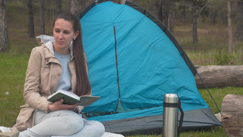 A young girl with long hair is sitting near a blue tent in the forest and Live Action
