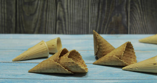 Ice cream cones, isolated on blue wooden surface. Waffles for ice cream Footage