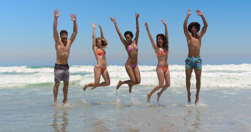 Young friends jumping together at beach 4k Live Action