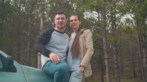 A guy and a girl are standing, leaning on a car in the forest. The guy shows the Footage