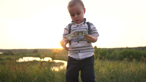 A cute small boy looks with interest at a hundred dollar banknotes, slow motion Footage