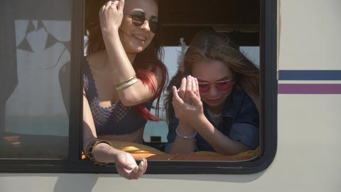 Two young woman is happy and watch to nature frome auto trailer window Footage