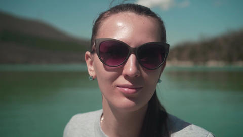 A young woman in sunglasses sits by the lake on a spring day, relaxing in nature Footage