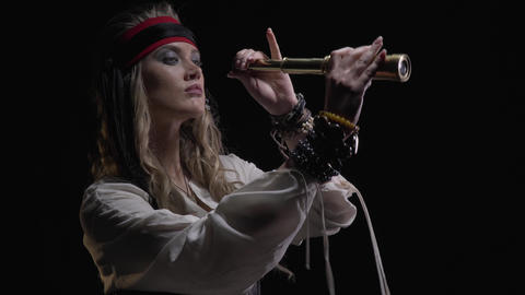 Female pirate in low lighting is standing in low lighting with her spyglass, 4k Live Action