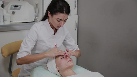 Beautiful woman doing facial massage at the beauty salon Footage